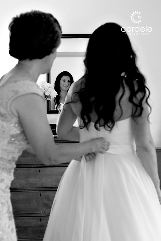 Black and White photo of bride getting into her wedding dress