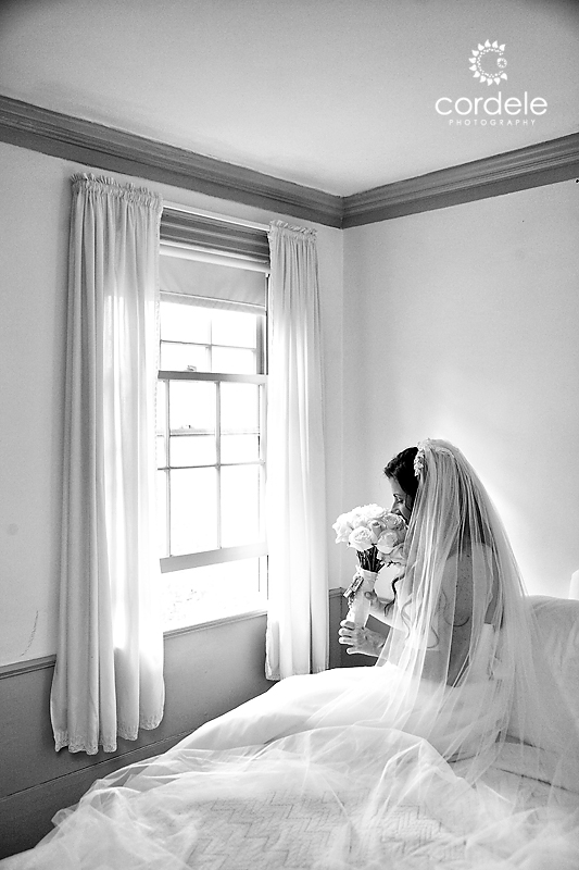 Bride sits on the edge of the bed looking out the window smelling her fowers.