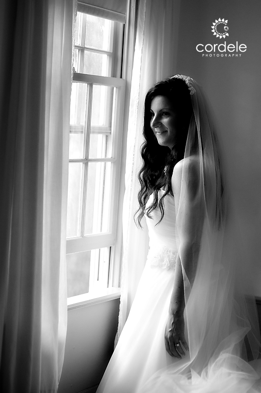 A bride looks out the window onto her wedding venue
