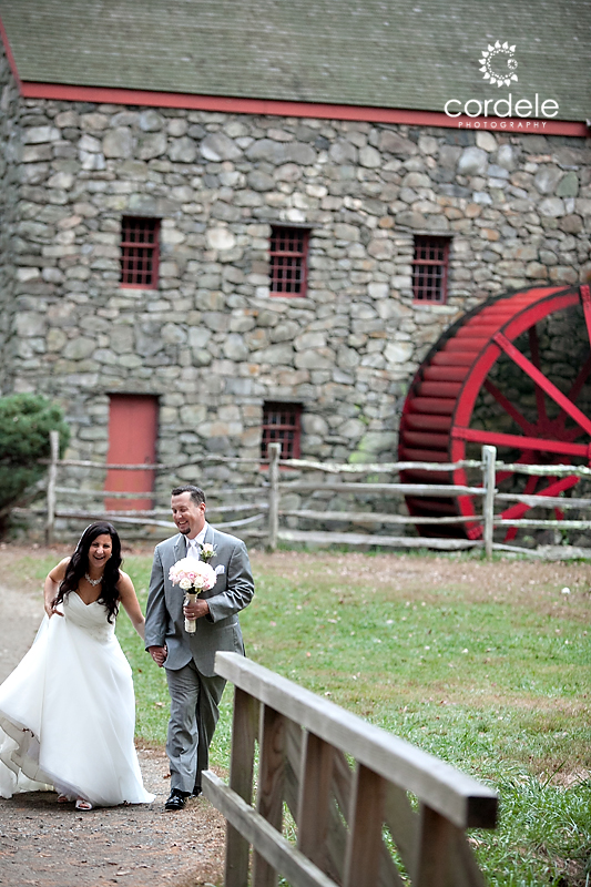 Bride and groom walk away from the Grist Mill at the Wayside inn in Sudbury.
