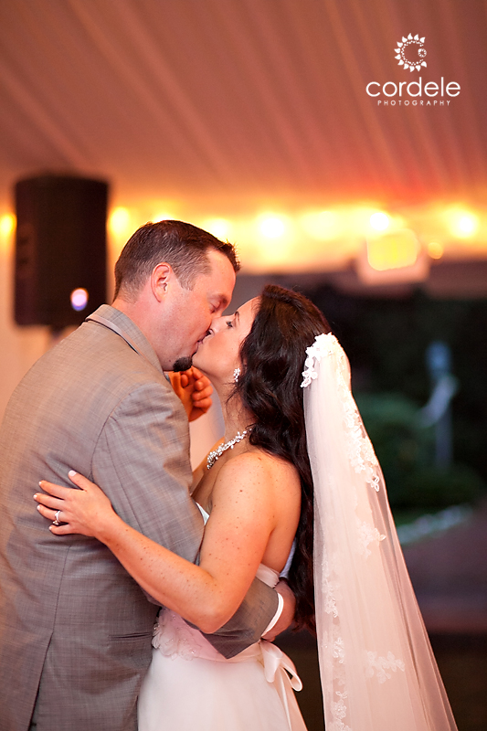 A COUPLE KISSES DURING THEIR FIRST DANCE AT THE WAYSIDE INN WEDDING TENT