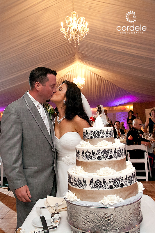 A bride and groom cut their cake in the tent at the Wayside Inn in Sudbury MA