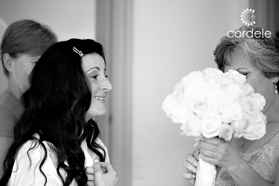 A Bride looks at her mom holding flowers in a black and white photo