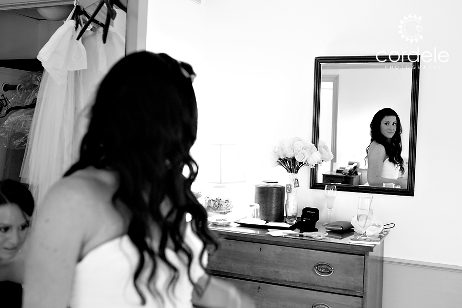 Bride looks in the mirror at Wayside Inn as she gets ready