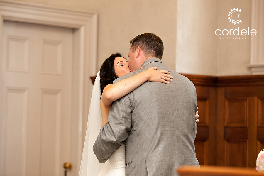 A first kiss of a bride and groom at the Mary Margaret Chapel in Sudbury