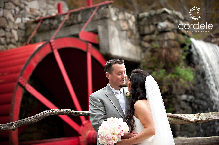 A bride and groom get their photos taken at the Grist Mill in Sudbury