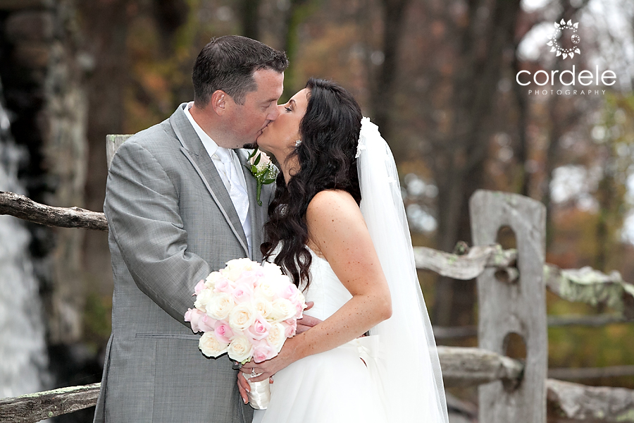 A couple kisses by the Grist Mill in Sudbury