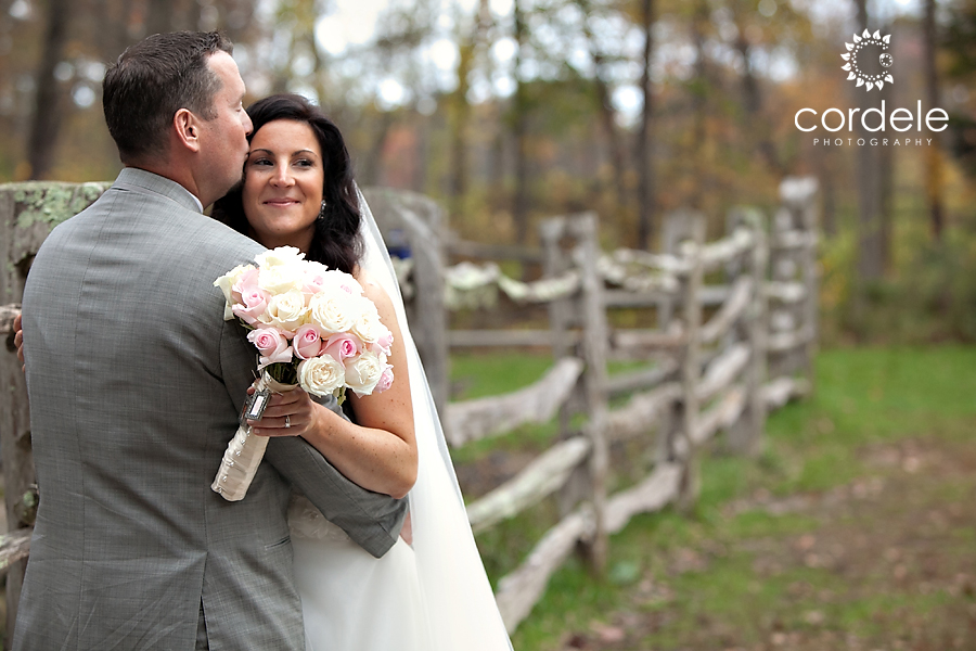 A couple gets their portrait taken on their wedding day at the Grist Mill in Sudury