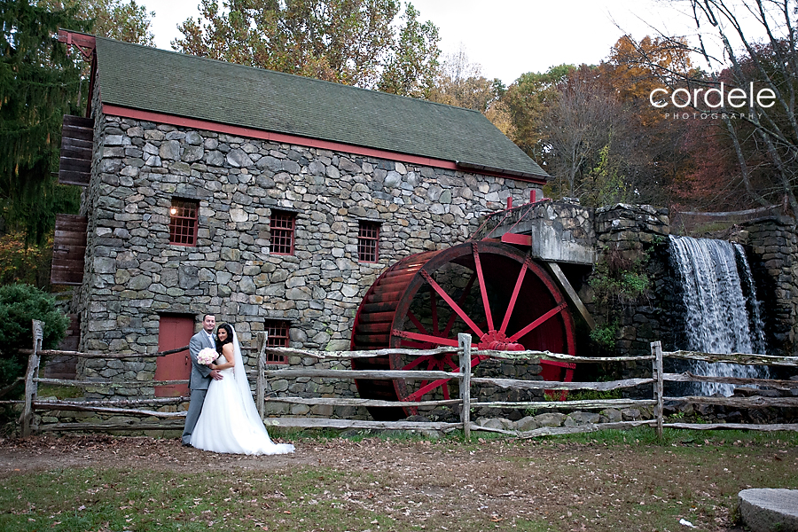 A Bride and groom get their formal wedding portrait taken outside the Grist Mill in Sudbury