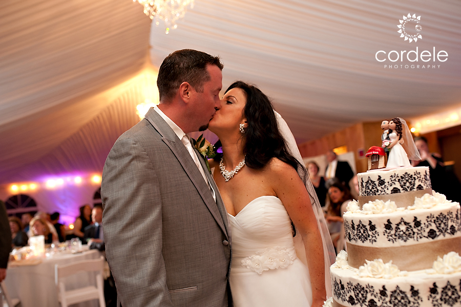 A bride and groom kiss after they cut the cake at the tent of the wayside inn